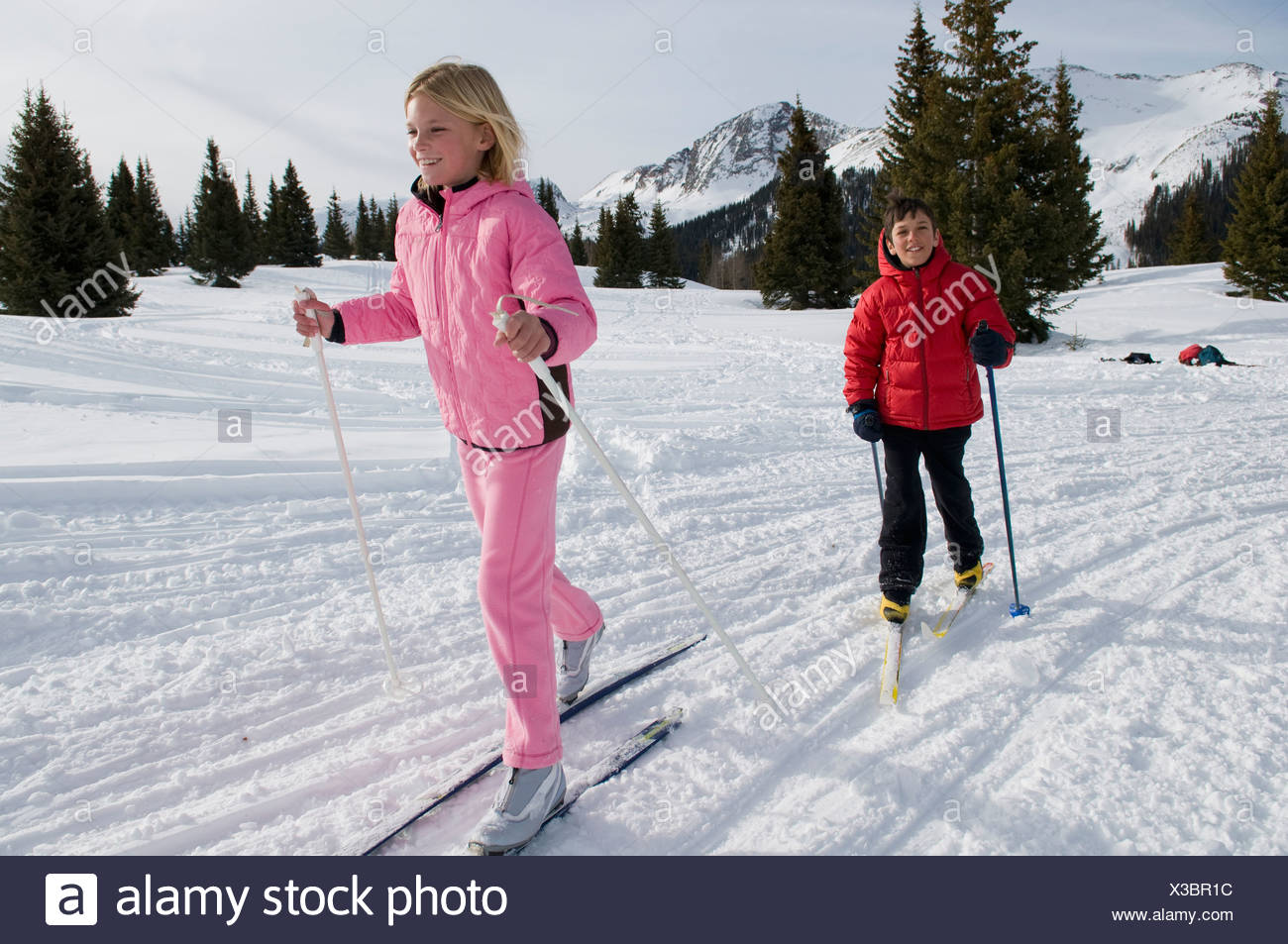A young girl and boy cross country skiing in the San Juan National Forest, Colorado. - Stock Image
