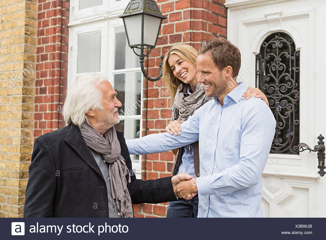 Mid adult couple by front door, senior man shaking hands - Stock Image