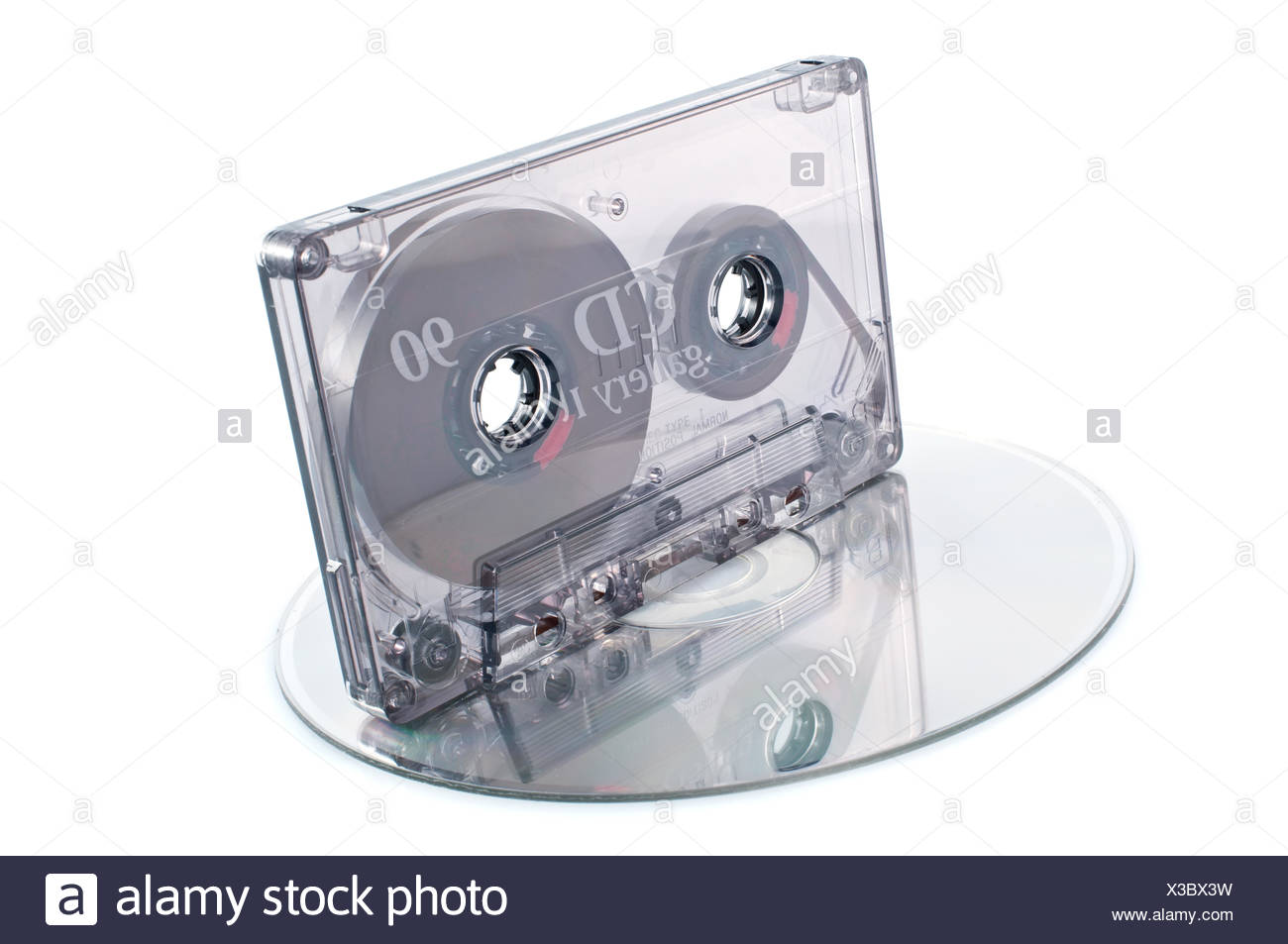 Analog audio tape cassette and digital compact disc on  white background - Stock Image