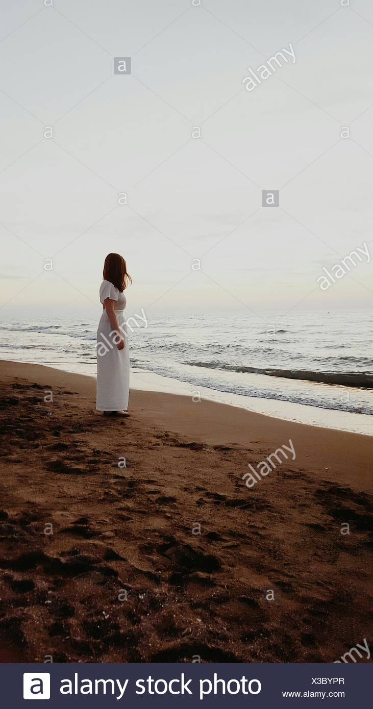 Full Length Of Woman Standing At Beach Against Sky - Stock Image