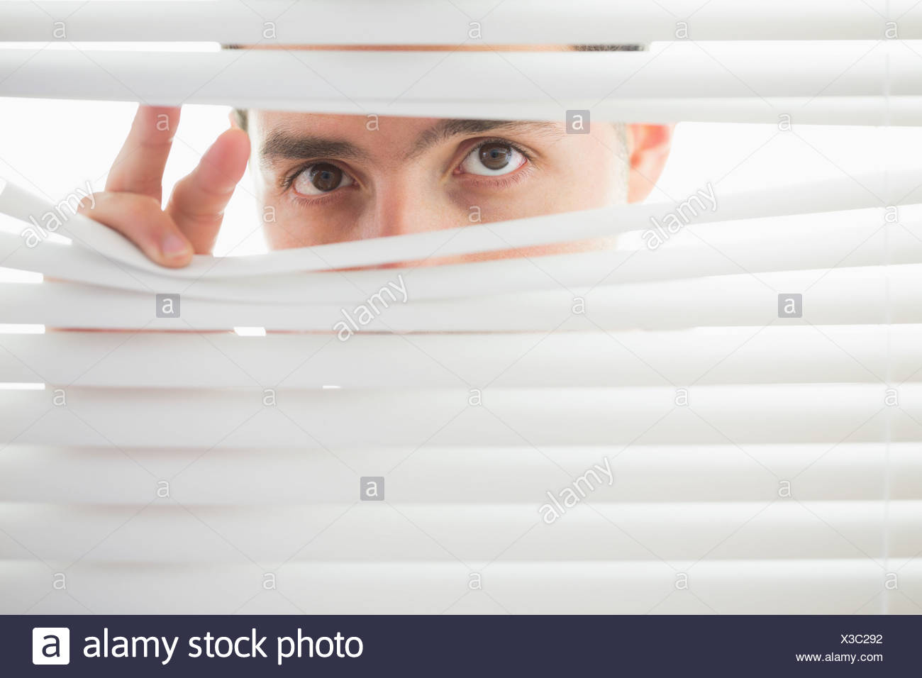 Suspicious male eyes spying through roller blind - Stock Image