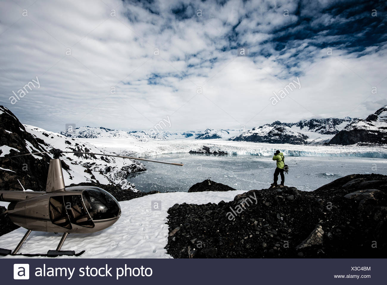 A man taking photos of a melting glacier with a helicopter waiting nearby.   Alaska, USA. - Stock Image