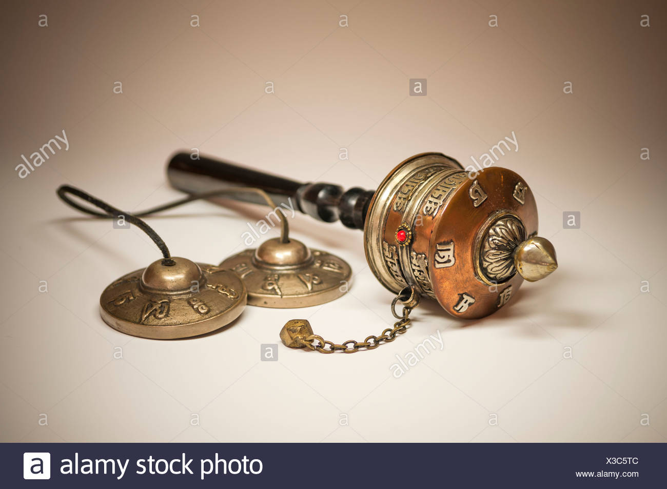 A Tibetan prayer mill and cymbals - Stock Image