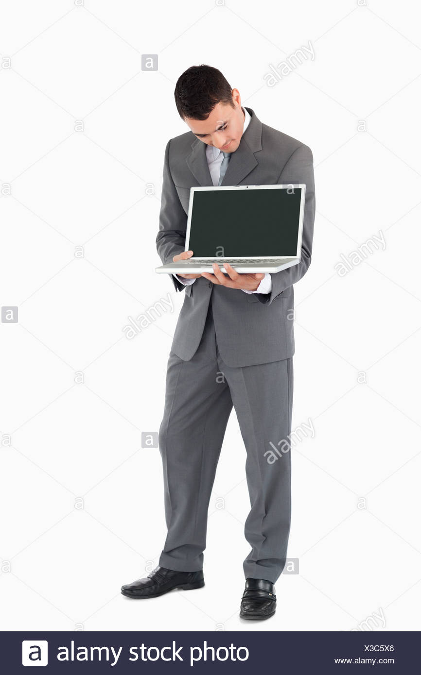 Businessman showing whats on his screen against a white background - Stock Image