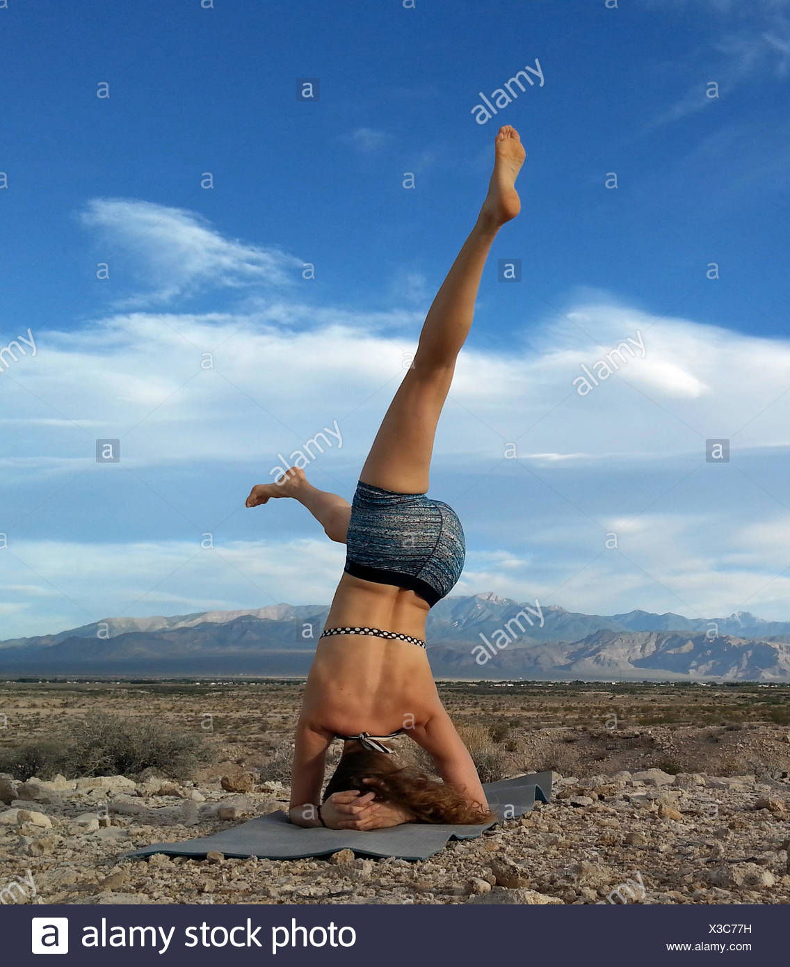Women doing a head stand in the desert, Nevada, America, USA - Stock Image