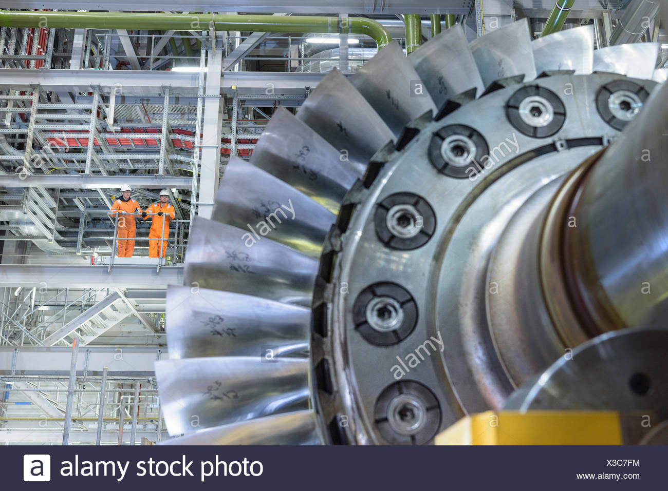 Workers on high level gantry in gas-fired power station - Stock Image