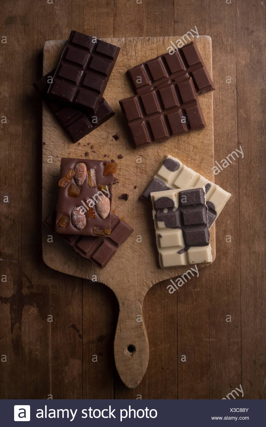 Multiple types of chocolate laid out on a rustic wooden cutting board. - Stock Image
