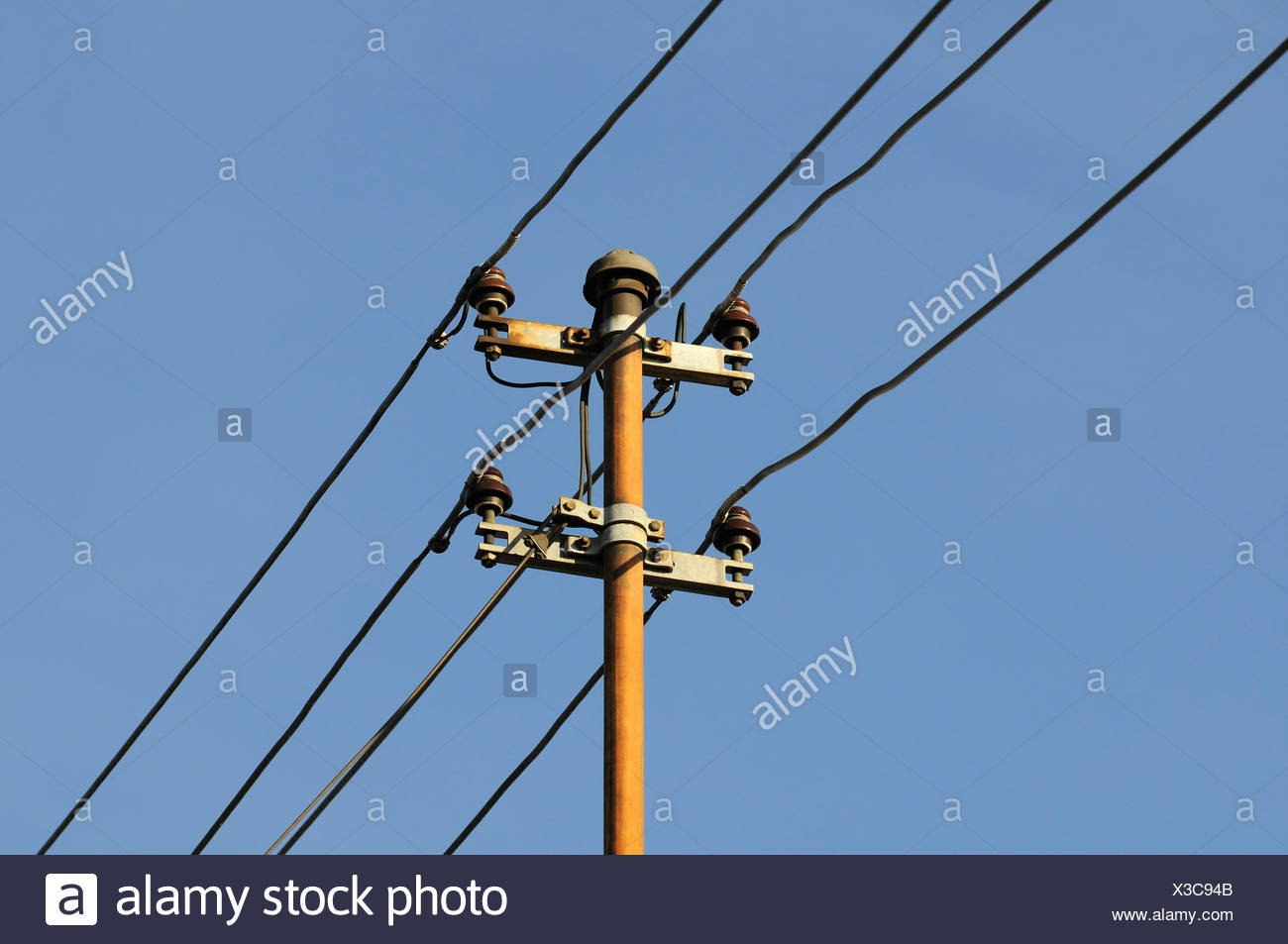 View of an old house utility pole with 4 wires and ceramic