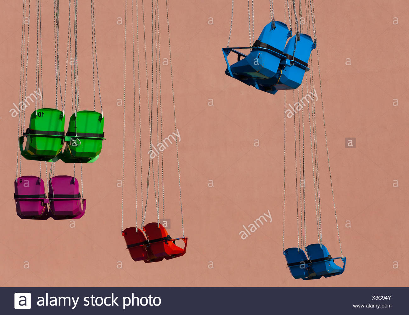 Empty seats of a Chairoplane or swing carousel in front of a house facade, Berlin, Germany, Europe - Stock Image