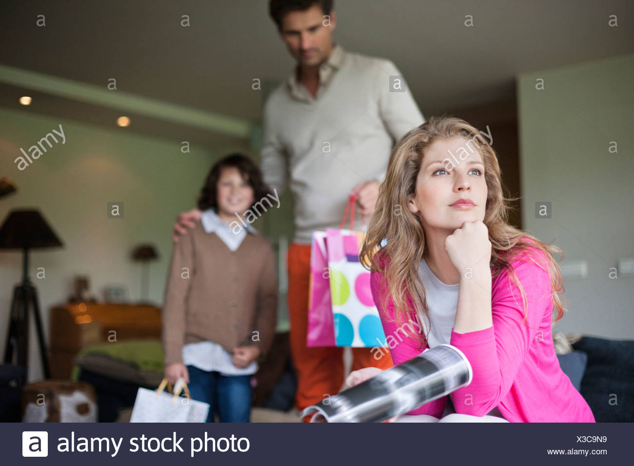 Woman thinking on couch with her husband and son holding