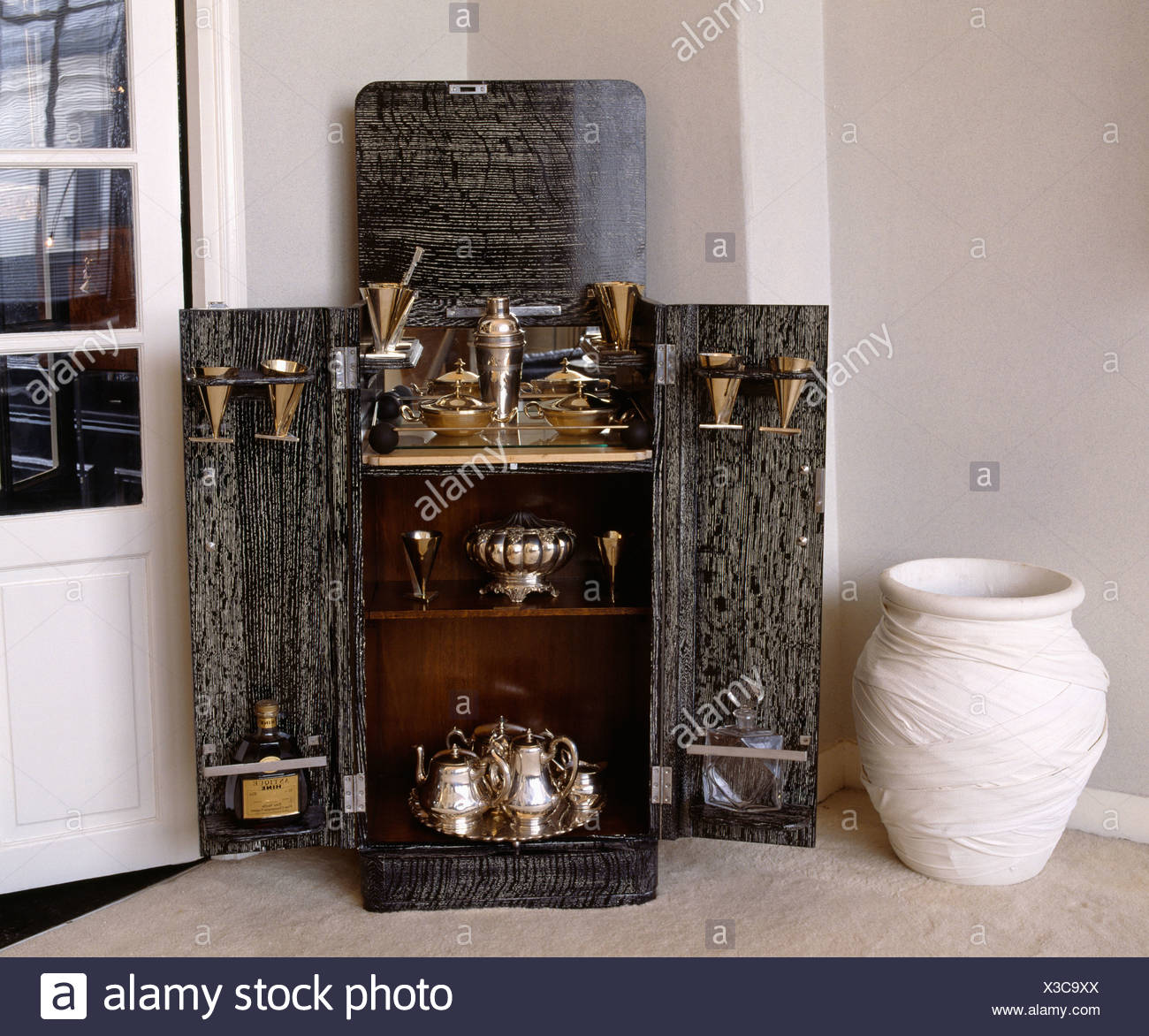 Close Up Of Large White Pot Beside Gray Marble Effect Thirties Cocktail  Cabinet With Chrome Glasses And Shakers