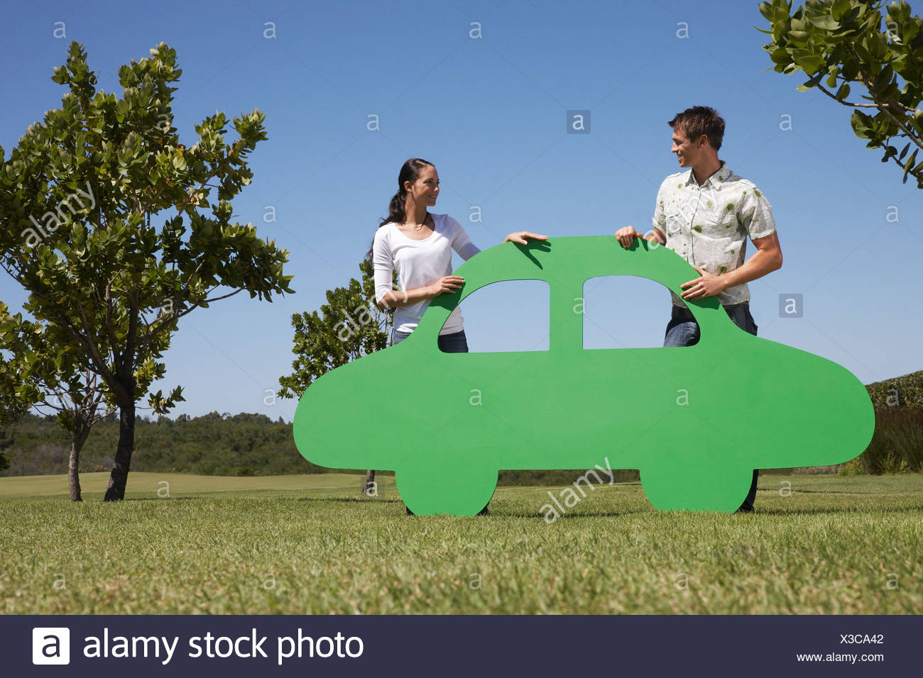 Couple standing with cutout car - Stock Image