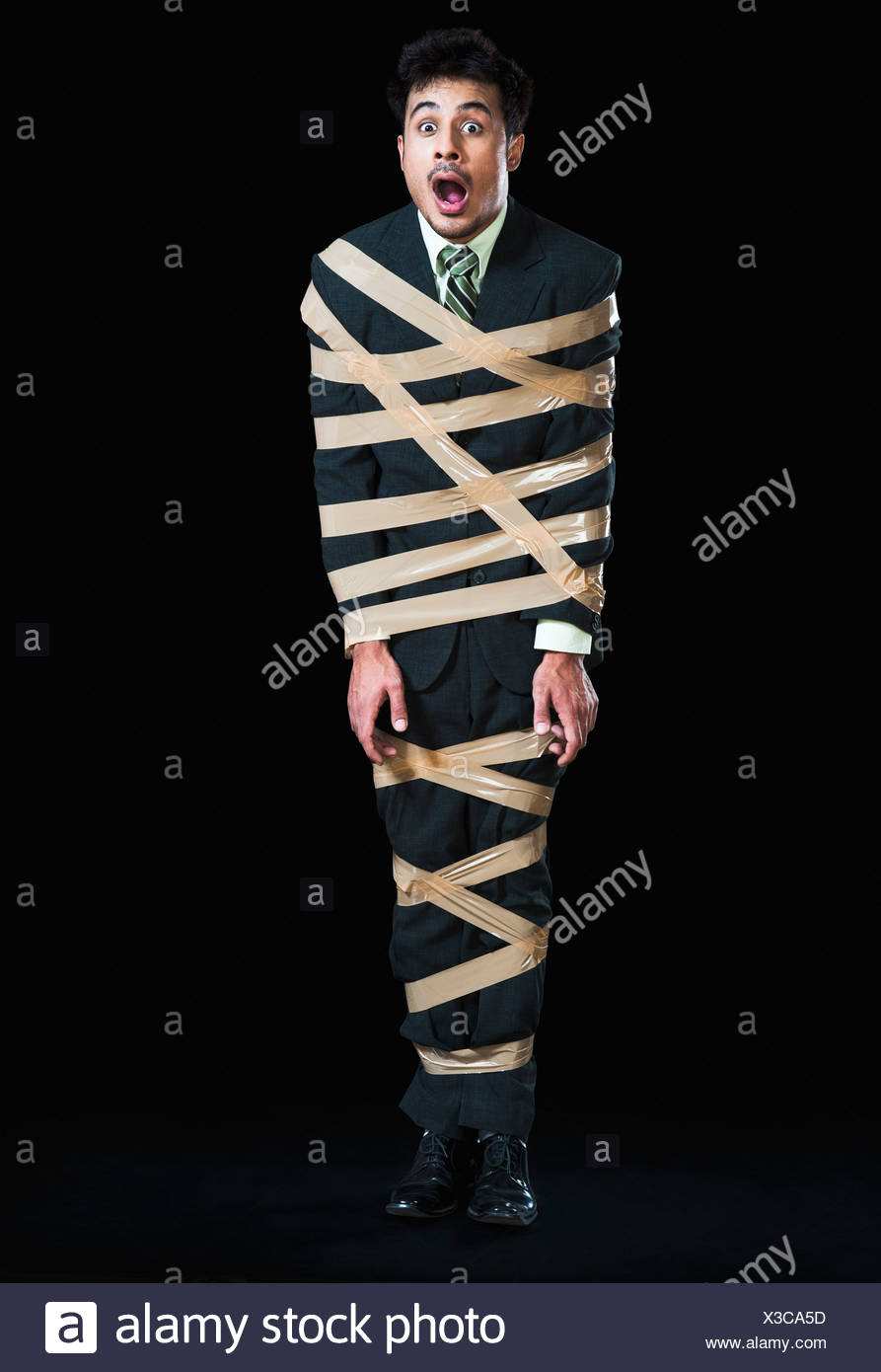 Businessman tied up with adhesive tape looking shocked - Stock Image