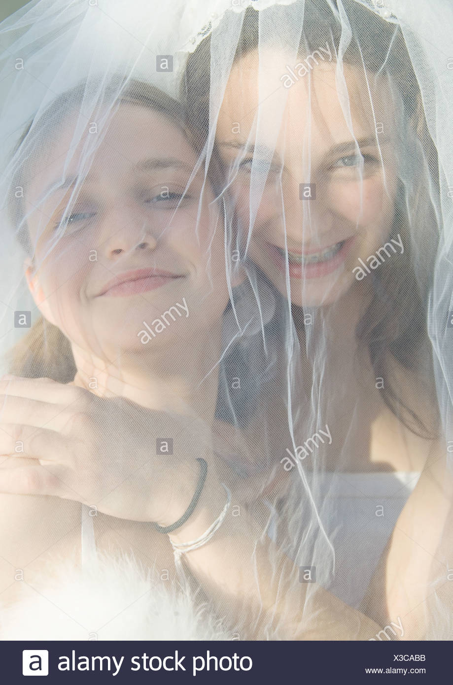 Preteen girls behind wedding veil - Stock Image