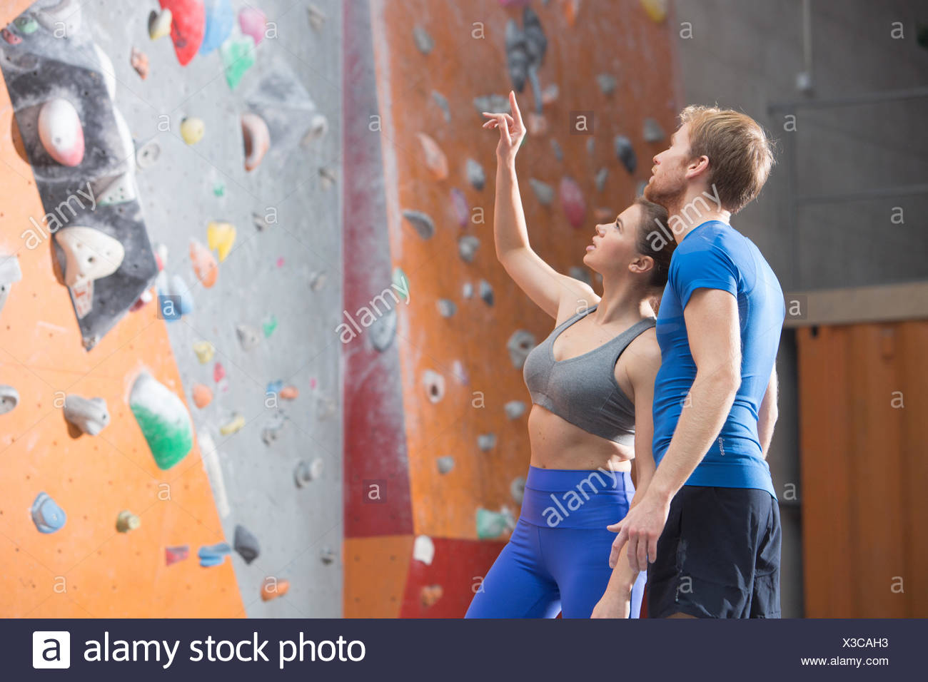 Man and woman discussing by climbing wall in crossfit gym - Stock Image