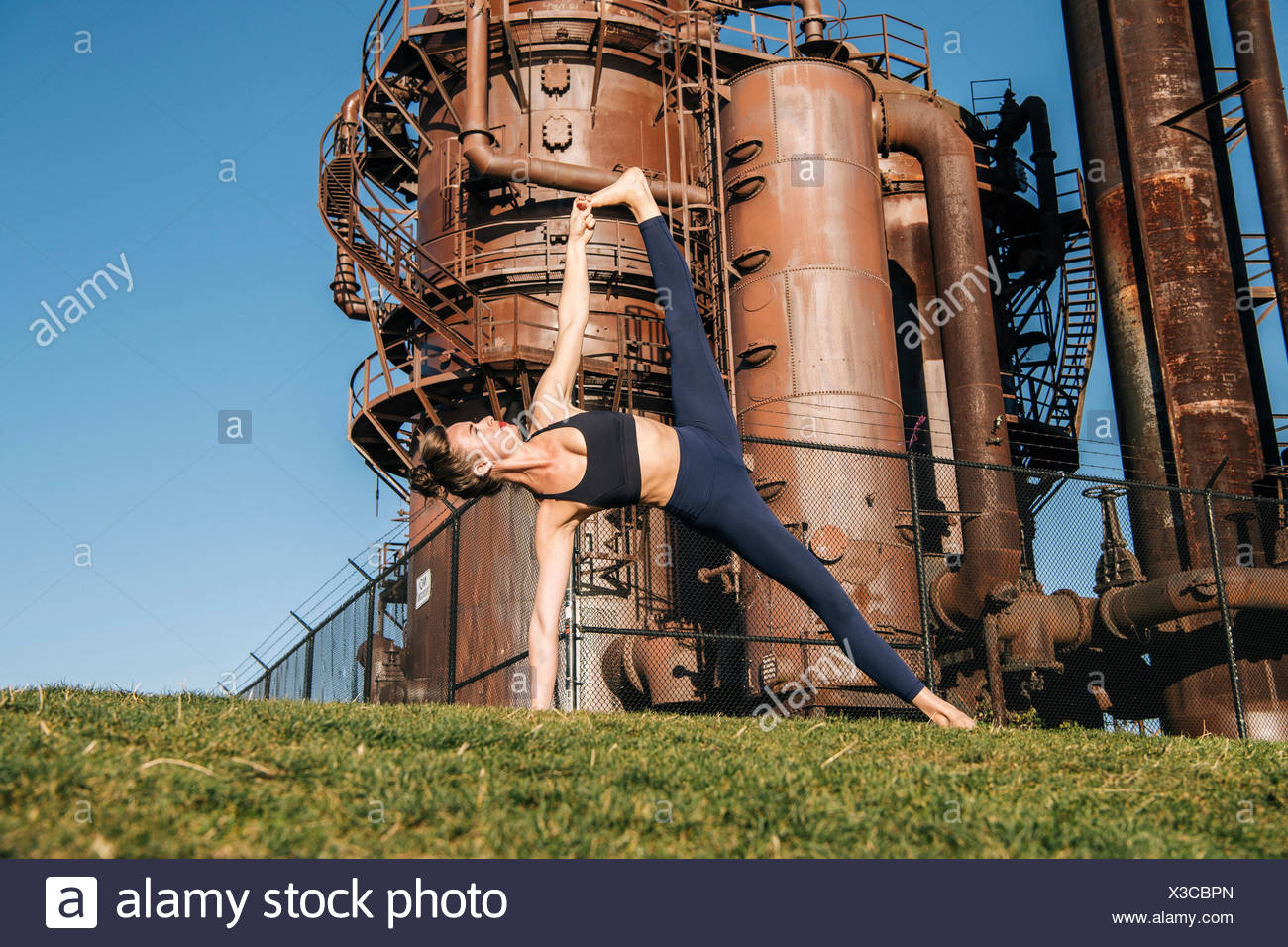 Young woman, near industrial works, in yoga position - Stock Image