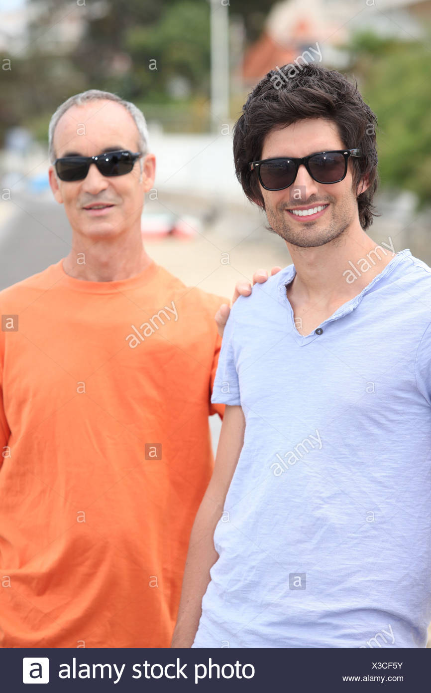 Father and grownup son wearing shades - Stock Image