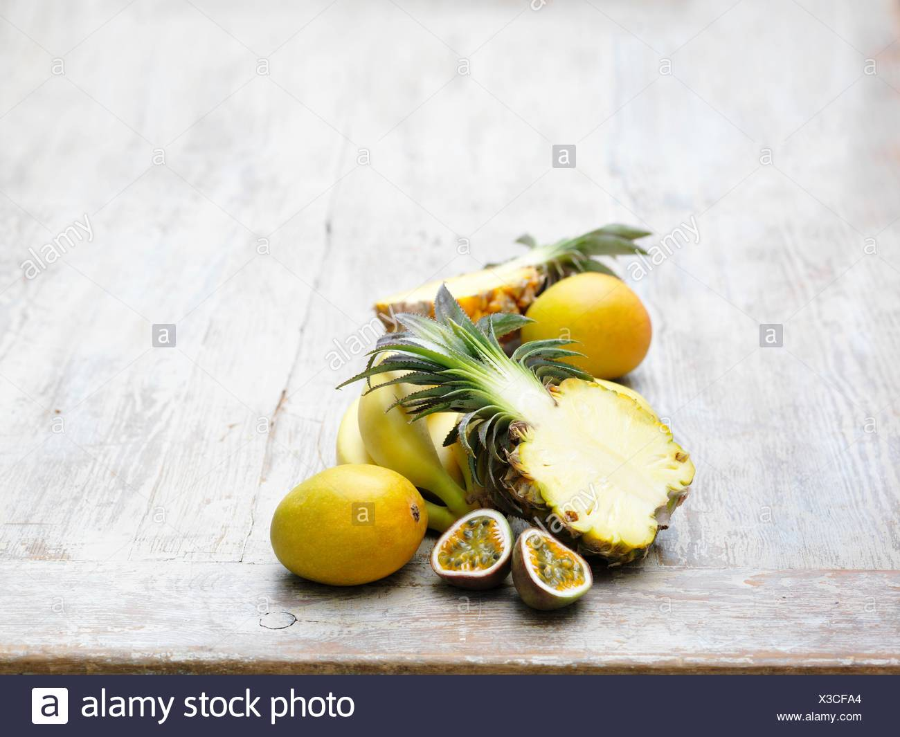 Ingredients for tropical juice on whitewashed wooden table - Stock Image