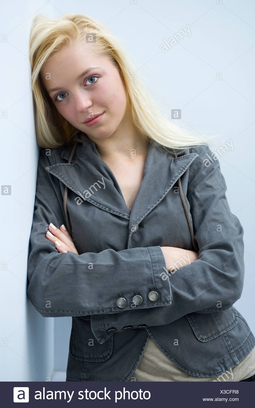 Young woman leaning against wall with arms folded, portrait - Stock Image