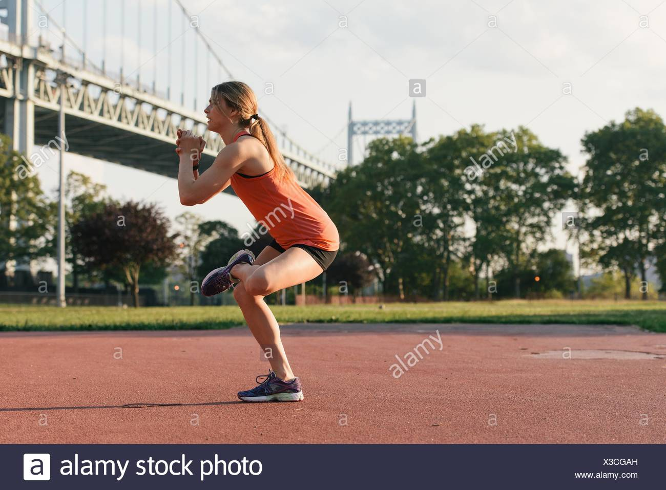 Young woman working out, stretching, outdoors - Stock Image