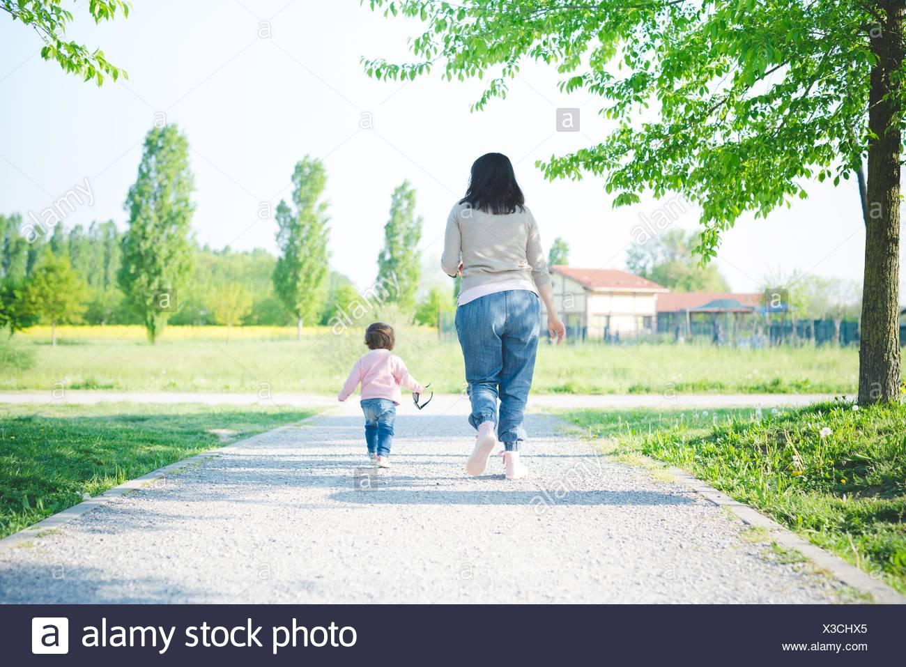 Rear view of female toddler toddling with mother in park - Stock Image