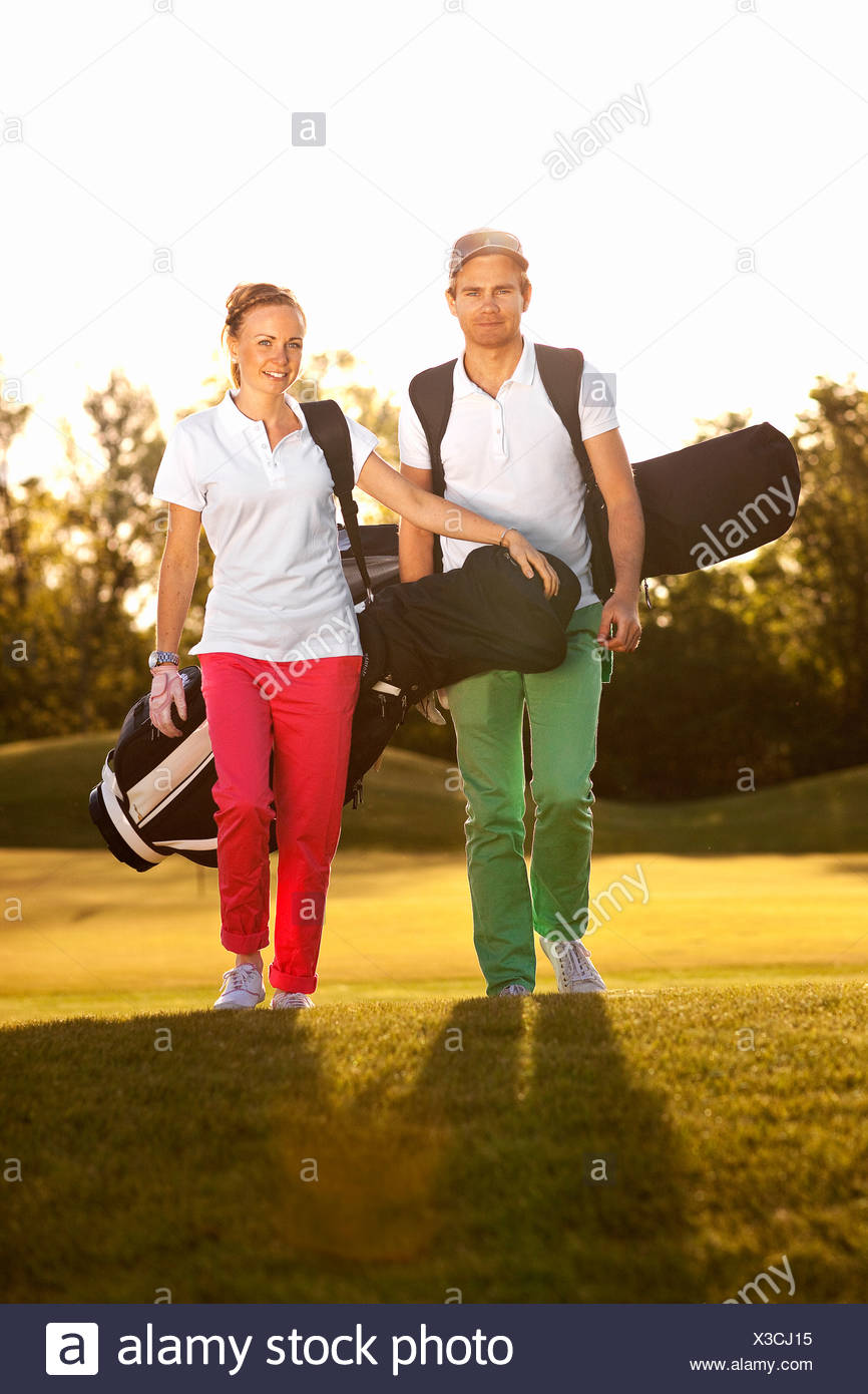 Young couple with golf bags - Stock Image