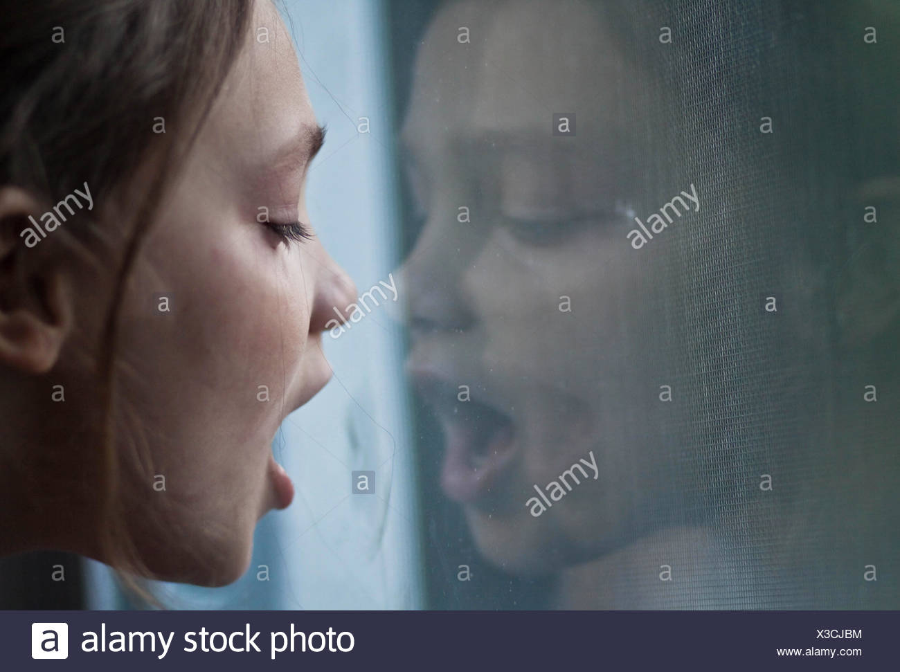 Close-up of girl breathing on window - Stock Image