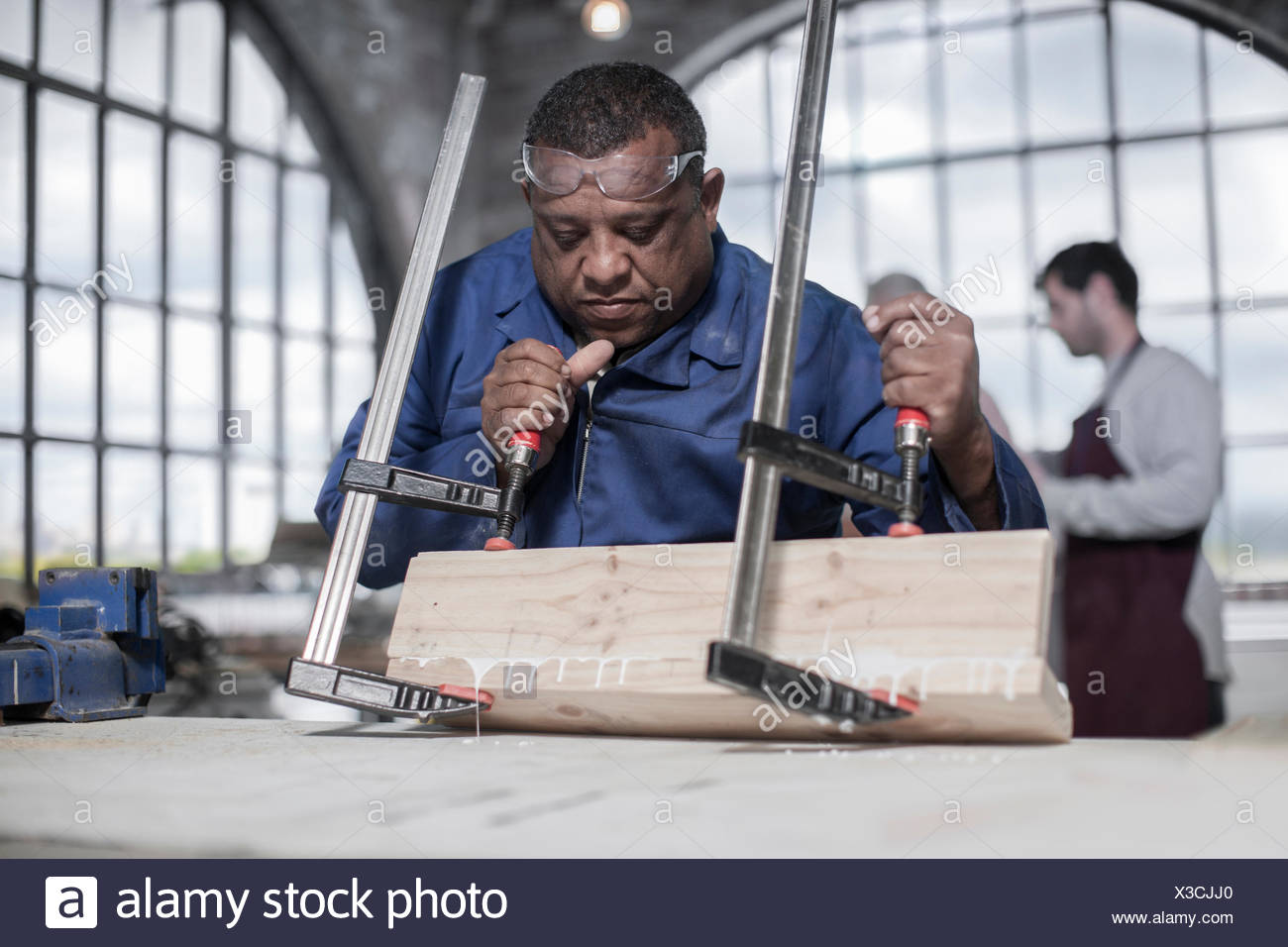 Carpenter gluing and clamping wood in workshop - Stock Image