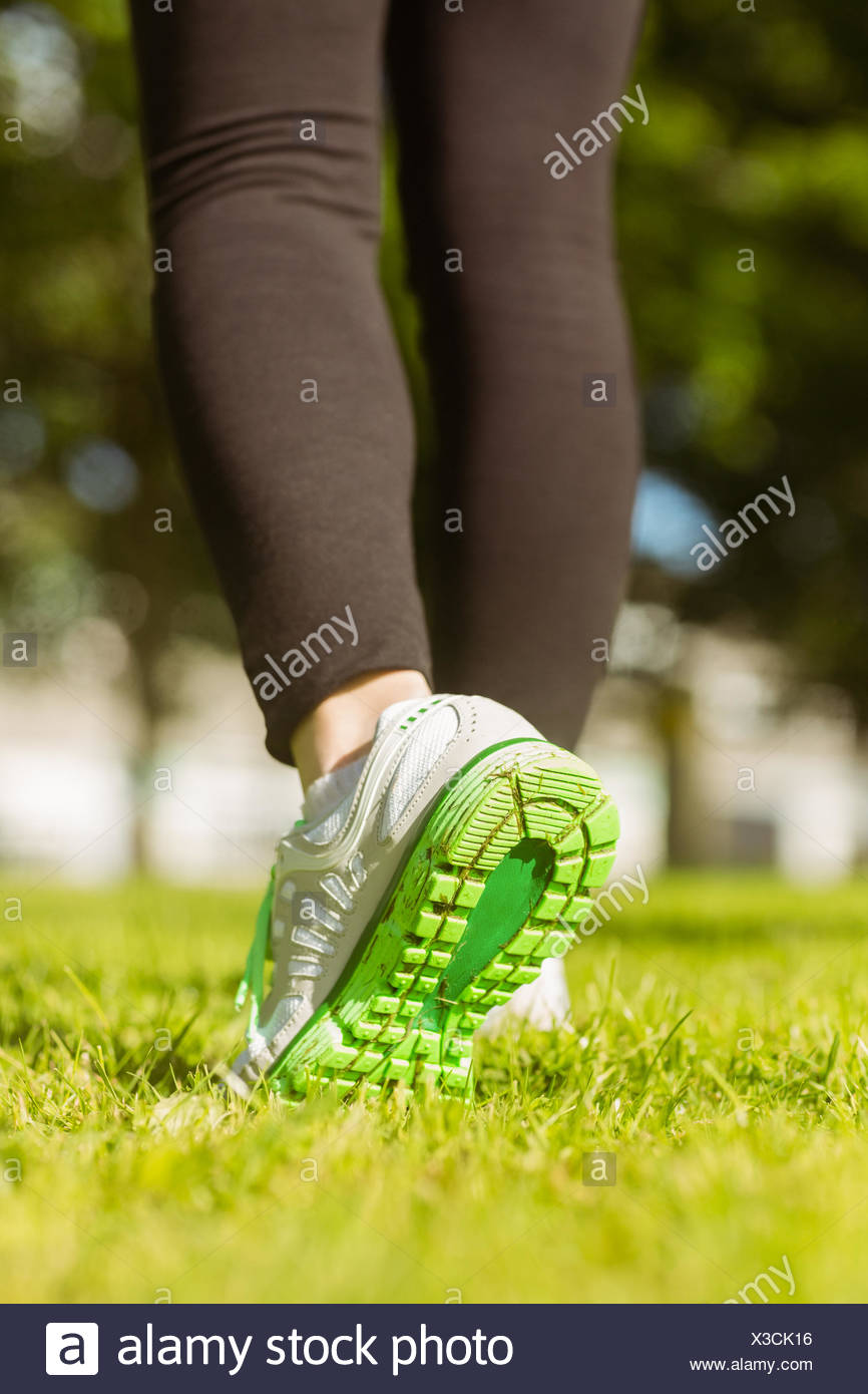 Woman in sports shoes jogging at park - Stock Image