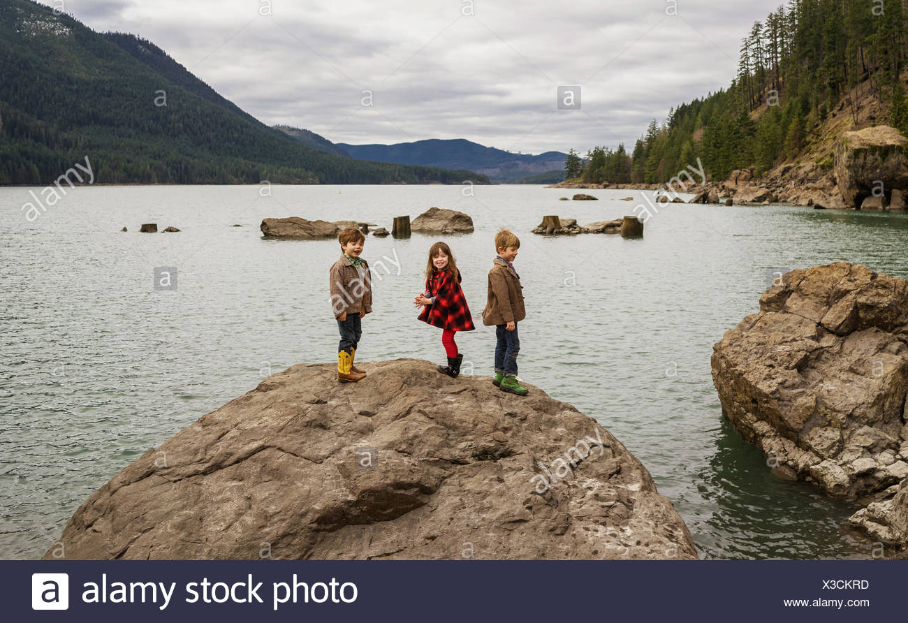 Three children standing on rock laughing in a river valley - Stock Image