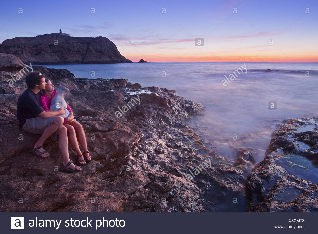 France, Corsica, L'Ile Rousse, rock coast, couple, dog, sunset, - Stock Image