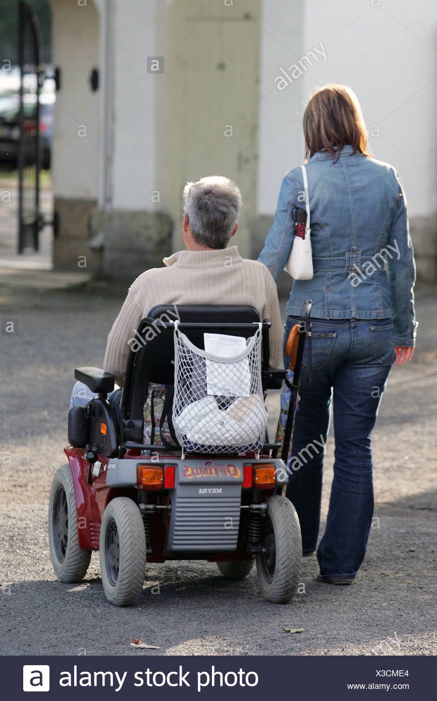 Dresden, a woman accompanied by a pensioner in a wheelchair - Stock Image