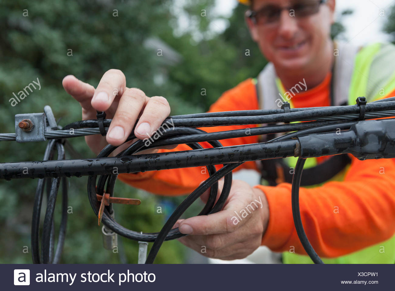 Cable lineman storing old cable to guy-wire from a bucket truck - Stock Image