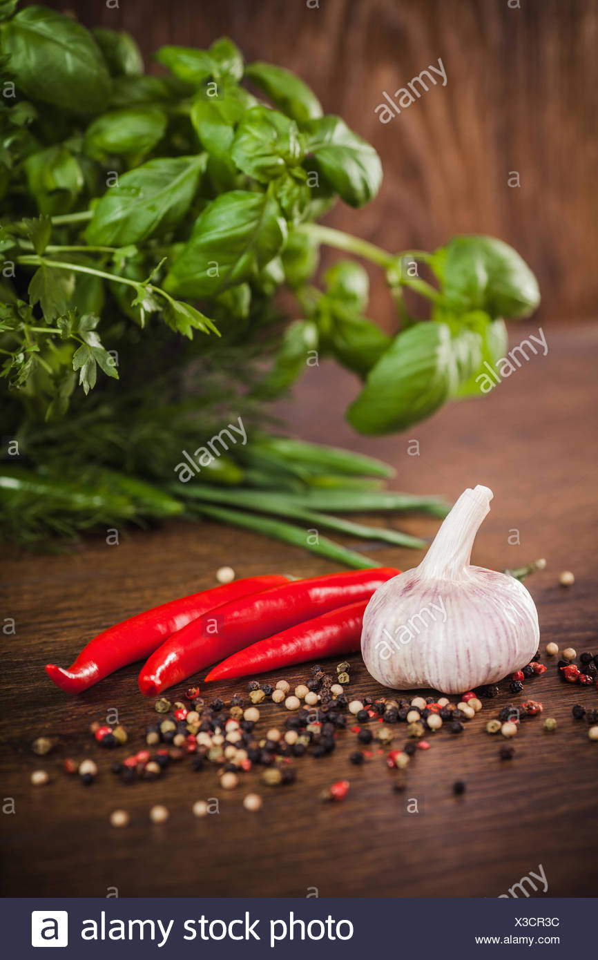 Chillies, garlic and herbs on a wooden table - Stock Image
