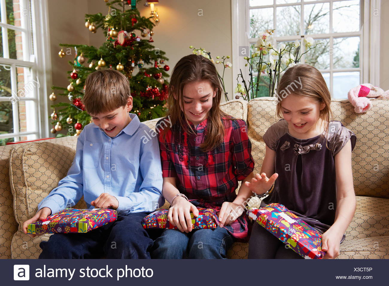 Children opening Christmas gifts Stock Photo: 277492258 - Alamy