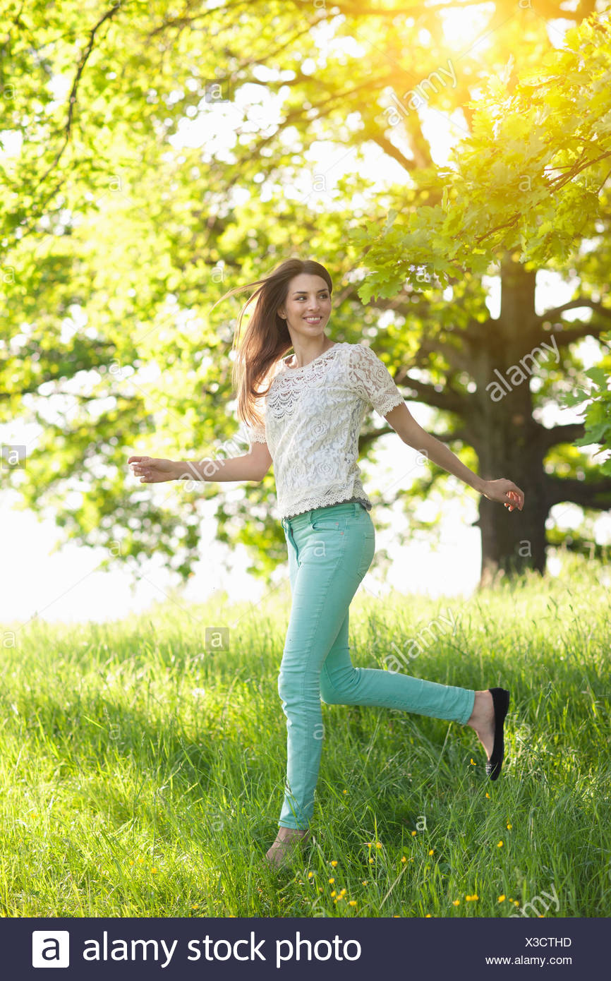 Young woman running through meadow - Stock Image