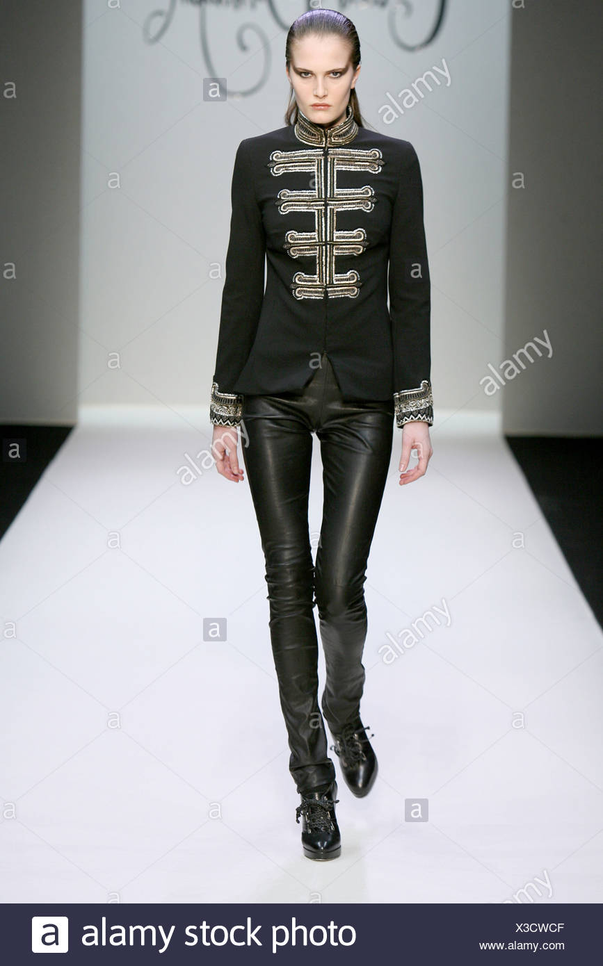 Collette Dinnigan Paris Ready to Wear Autumn Winter Model wearing tight black leather trousers a black miliary style jacket Stock Photo