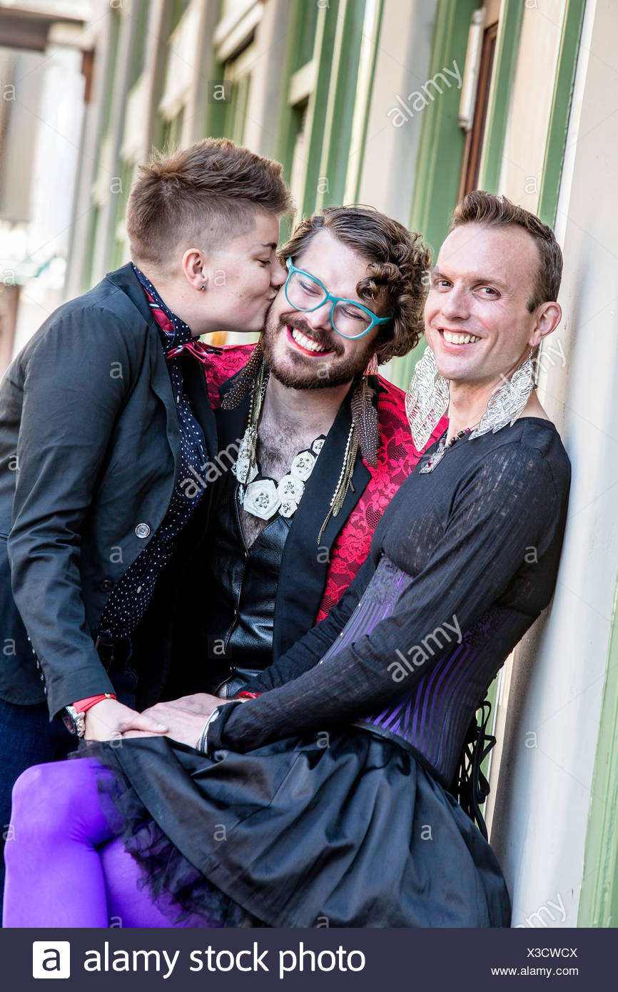 A Kiss Among Three Gender Fluid Friends - Stock Image