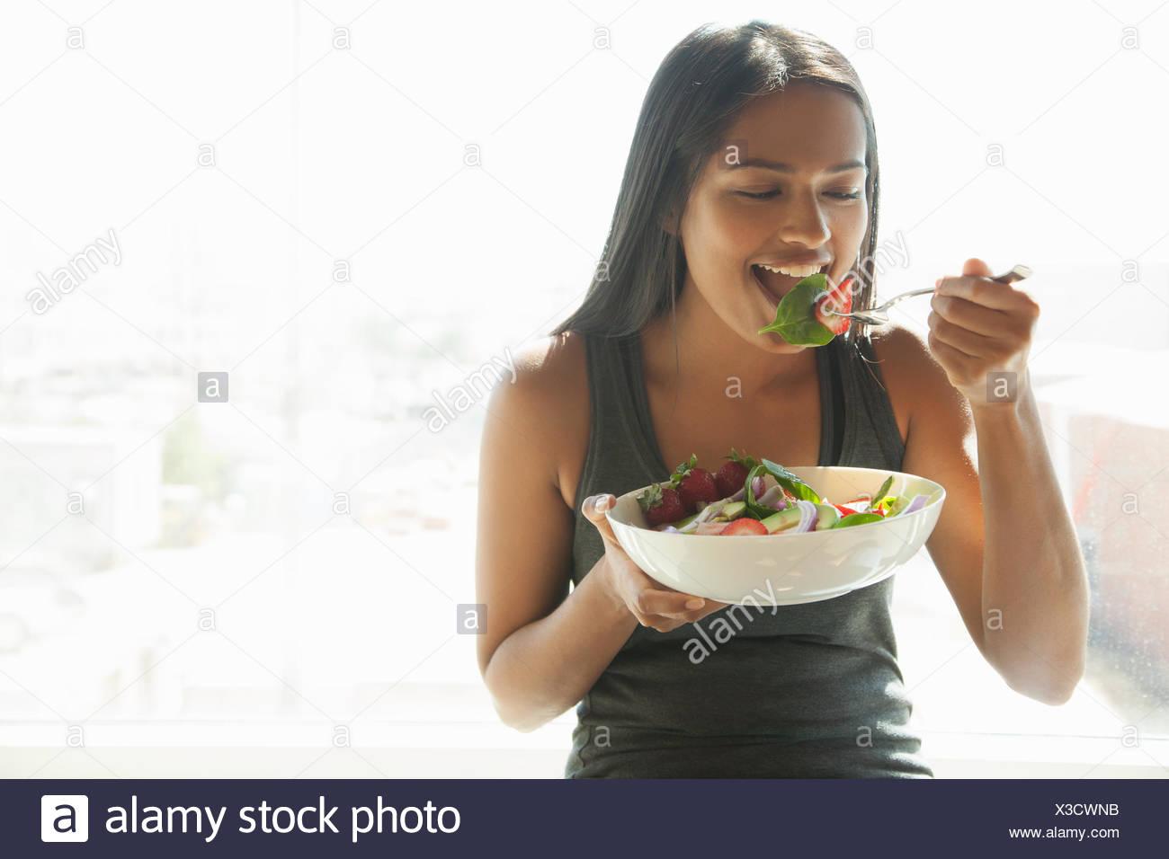 Woman eating salad at home - Stock Image