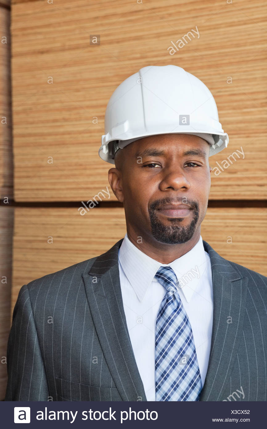 Portrait of an African American male engineer with wooden planks in background - Stock Image