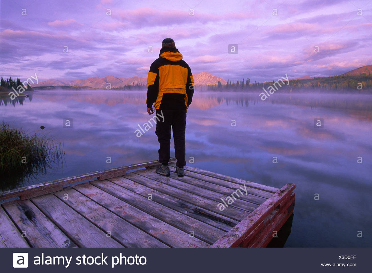 Hiker on Dock at Sunrise, Jackfish Lake, near confluence of North Canol and Robert Campbell Highways, south of Ross River, YT - Stock Image