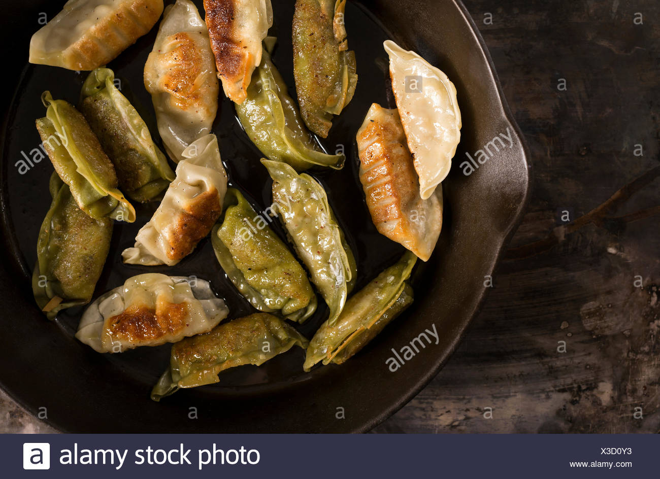 Variety of pan fried pork and vegetable pot stickers in a skillet on a rustic metal surface. - Stock Image