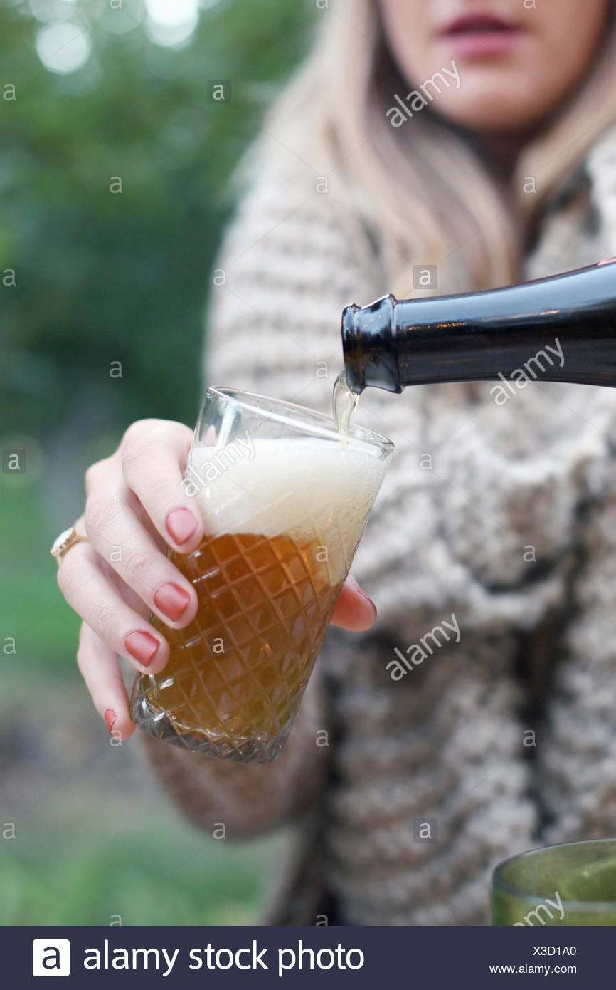 Apple orchard. Woman pouring a glass of cider. - Stock Image