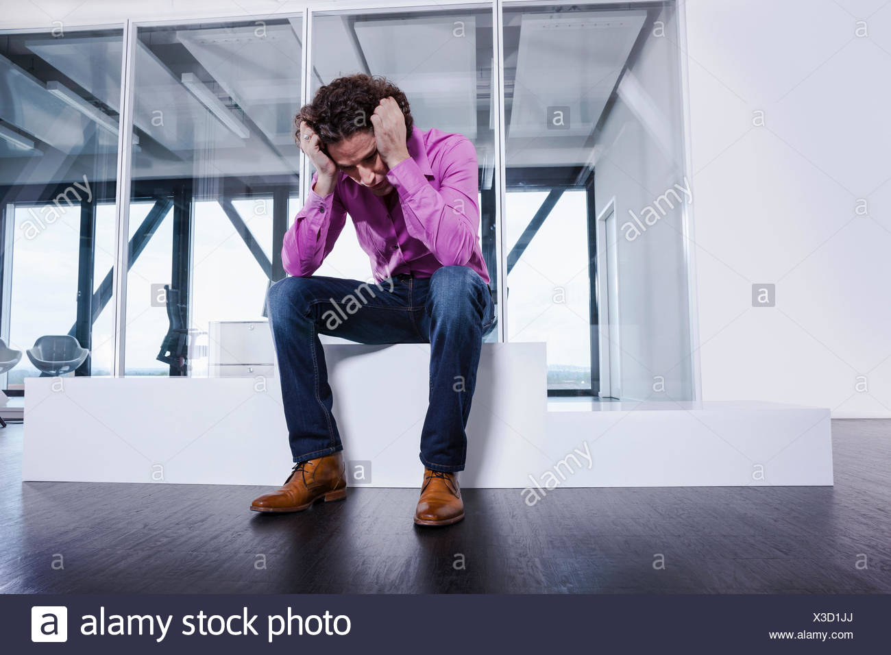 Mature man sitting on podium with head in hands - Stock Image