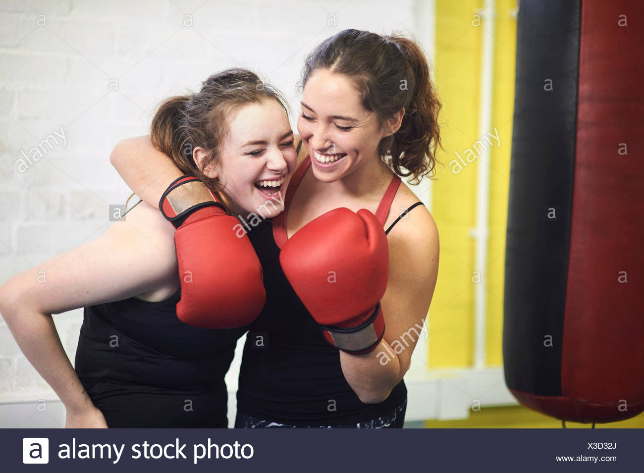 Two female boxing friends pretending to punch in gym - Stock Image