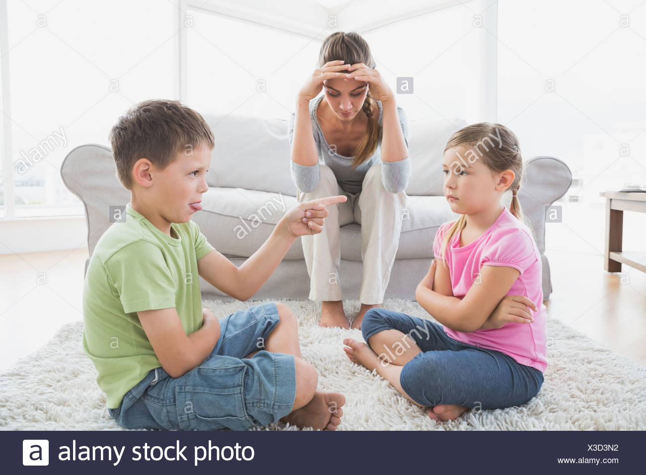 Fed up mother listening to her young children argue - Stock Image