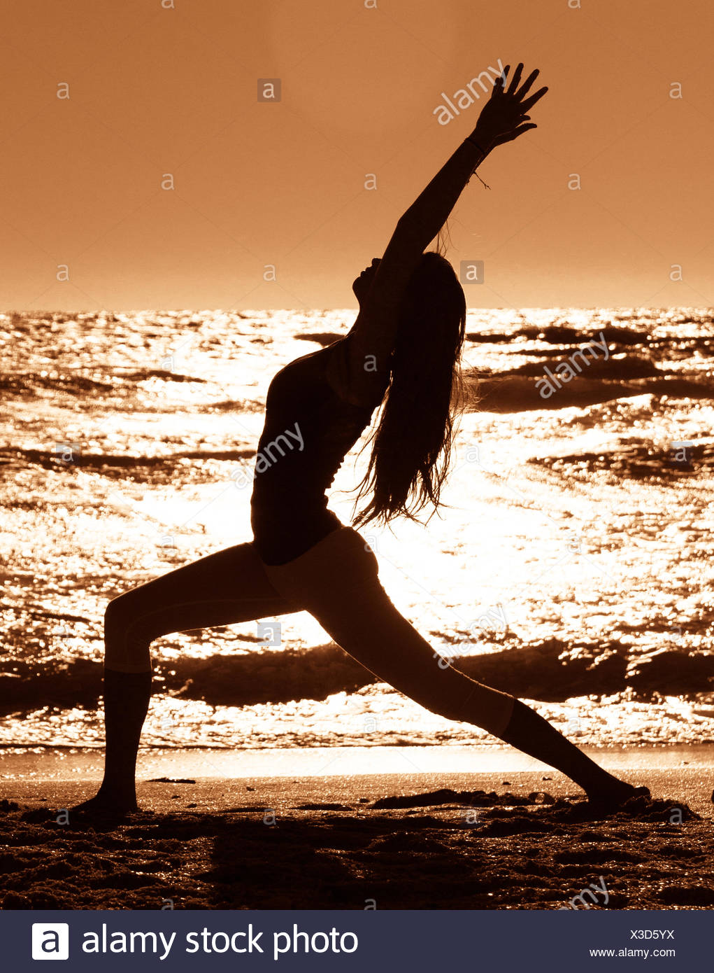 Silhouette of Woman practicing warrior 1 yoga pose on beach - Stock Image