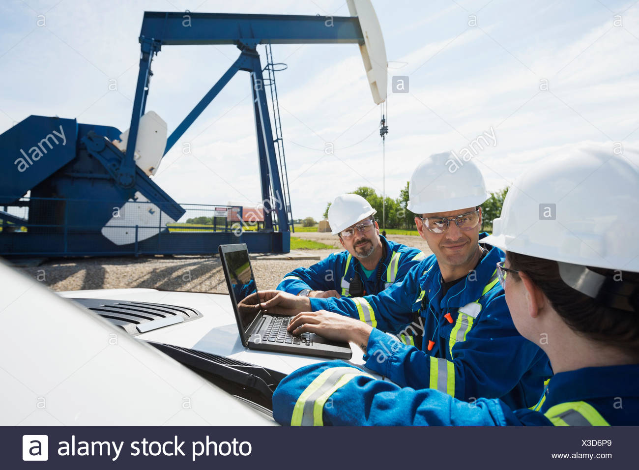 Workers with laptop talking near oil well - Stock Image