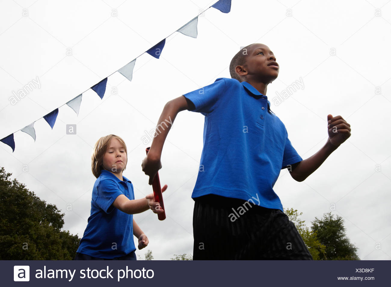 School boy passing baton to teammate - Stock Image