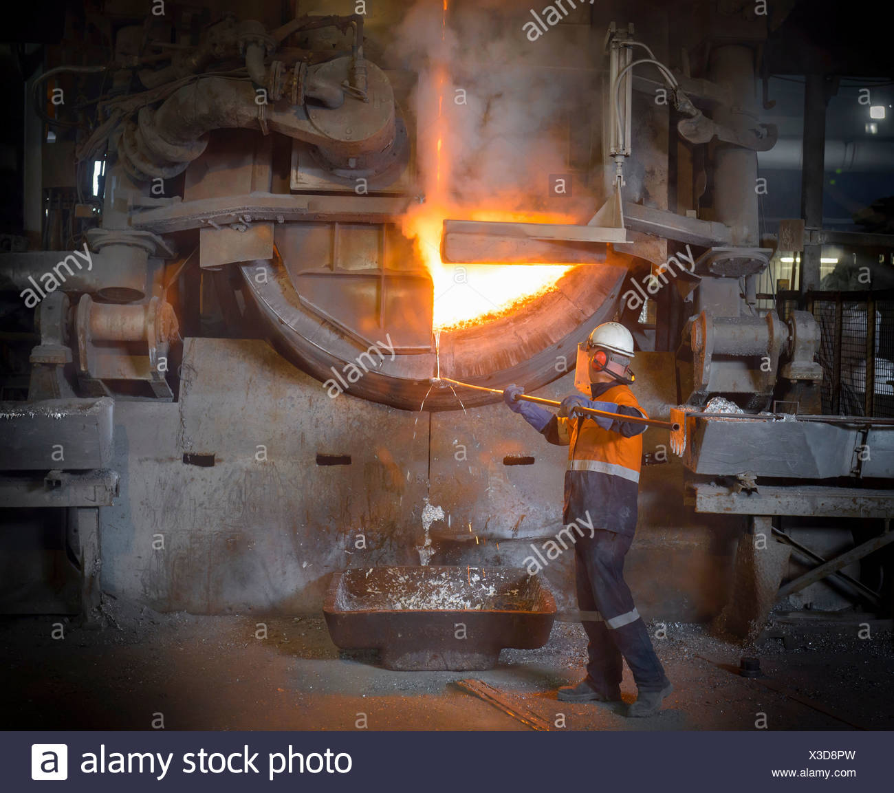 Worker removing liquid aluminum from furnace at recycling plant - Stock Image